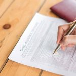 Hand with pen over  Travel Aviation Insurance application form a
