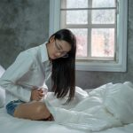 young-woman-suffering-from-abdominal-pain-while-sitting-bed-home_38583-486